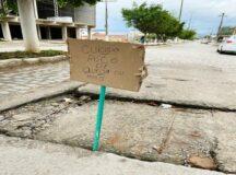 """Compesa: Moradores sinalizam buraco com placa """"Cuidado! Risco de queda ou morte"""""""