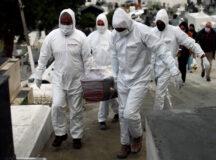 Funcionários de cemitério com roupa de proteção durante enterro de vítima da Covid-19 em Nova Iguaçu (RJ) 16/07/2020 REUTERS/Pilar Olivares